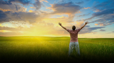 Picture of man in open field holing arms open toward world